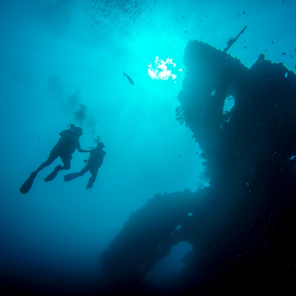 Two divers captured from below approach a wreck - © www.michaelevansphotographer.com 2016